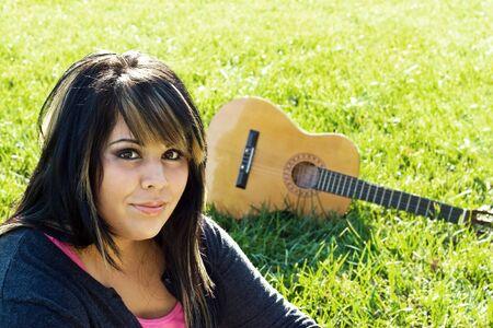 highlights: Una mujer joven sentado en la hierba verde con una guitarra ac�stica en segundo plano. Profundidad de campo.