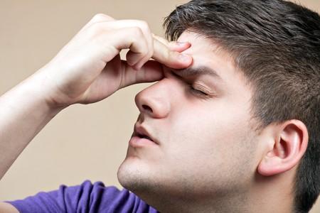 ontbering: Jonge man heeft een intense hoofdpijn. Hij zou kunnen worden ervaren stress tijdens een tijd van economische crisis of andere problemen. Stockfoto