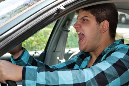 enraged: An irritated young man driving a vehicle is expressing his road rage.