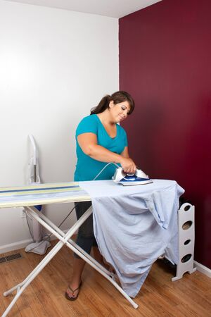 A young woman at home pressing some clothes on an ironing board. photo