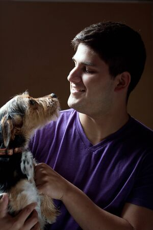 Low key portrait of a young man holding a cute mixed breed terrier dog isolated over a dark background. photo