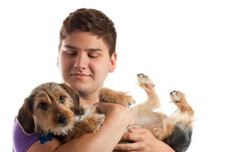 High key portrait of a young man holding a cute mixed breed dog isolated over white. Shallow depth of field with focus on the mans face. Stock Photo - 8204590