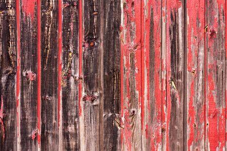 Een oude versleten schuur of houten hek met afgestoken rode verf.