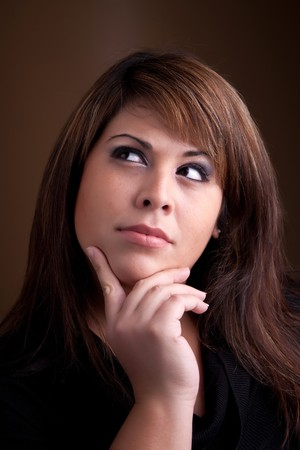 something: A pretty young Hispanic female posing with her hand on her chin thinks deeply about something on her mind.