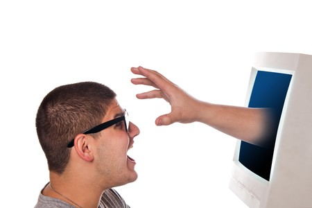 Nerdy young man looks frightened as a hand and arm reaches out from his computer monitor.  A great concept for identity theft or spyware.