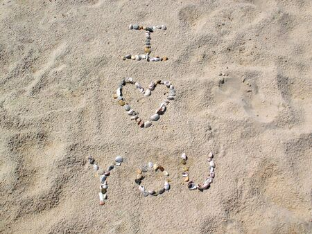 I love you with a heart shape symbol written out in the sand with seashells.   photo