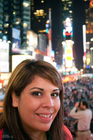 A young woman smiling as she stands in Times Square in New York City.   photo