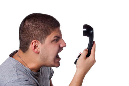 unprofessional: An angry and irritated young man screams into the telephone receiver over a white background.
