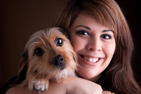beagle mix: A young woman in her 20s holds a cute mixed breed beagle yorkshire terrier dog.