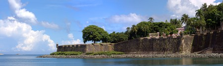 rico: The city boundary and old decaying wall of El Morro fort located in Old San Juan Puerto Rico. Stock Photo