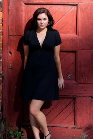 A pretty young woman in a black dress leaning against an old red doorway.  Stock Photo - 8294086