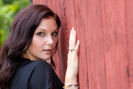 A pretty young woman in a black dress leaning against an old red doorway. Stock Photo - 8294084