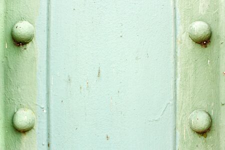 A light green painted metal background texture with four rusted bolts or rivets. photo
