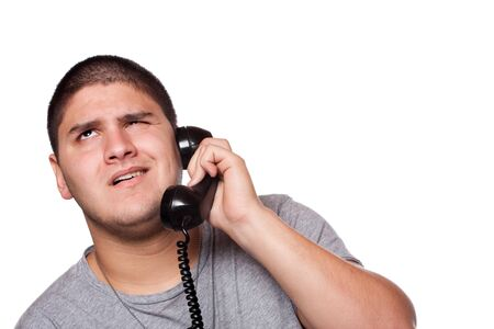 business skeptical: A young man listens on the telephone with an annoyed expression on his face.