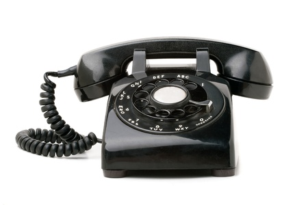 rotary phone: An old black vintage rotary style telephone isolated over a white background.