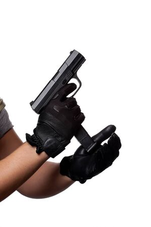 A man loading or unloading a clip into a black handgun isolated over white.  Works great for crime or home security concepts.