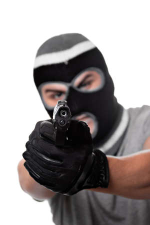 An angry looking man aiming a handgun at the viewer. Works great for crime or home security concepts. photo