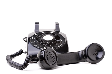 An old black vintage rotary style telephone off the hook isolated over a white background. photo
