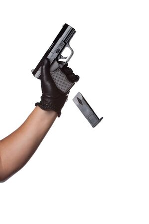 reloading: A man reloading a weapon drops the clip from a black handgun.  Works great for crime or home security concepts.
