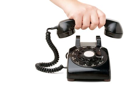 A hand  holding the handset of an old black vintage rotary style telephone isolated over white. Banco de Imagens