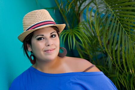 An attractive young Hispanic woman smiling with her hat and outdoors by some tropical foliage. Stock Photo