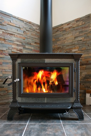 stove: A new cast iron wood stove burning hot with slate tile. Stock Photo