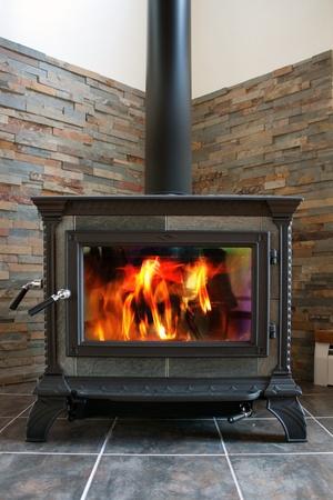estufa: Una madera de hierro fundido nueva estufa quema caliente con pizarra de azulejos y baldosas.