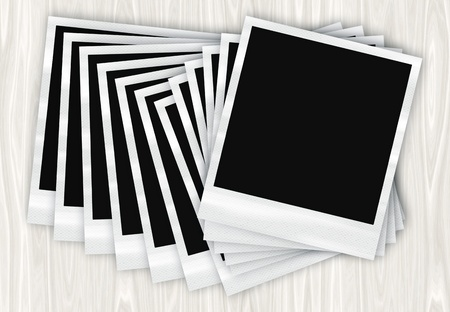 A pile of instant film photos arranged in a row on a wooden table. Stock Photo - 8433158
