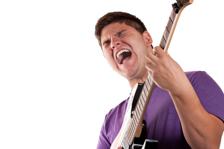 A man in his late teens rocks out while playing his electric guitar. photo