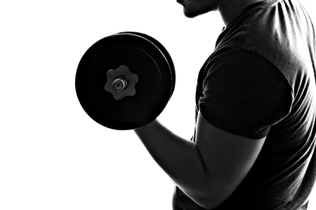 man lifting weights: Back lit silhouette of a young man lifting weights in black and white.