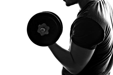 Silueta de iluminación posterior de un hombre joven, levantamiento de pesas en blanco y negro.