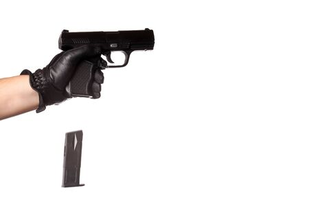 reloading: A man reloading a weapon drops the clip from a black handgun. Slight motion blur on the falling ammunition clip. Stock Photo