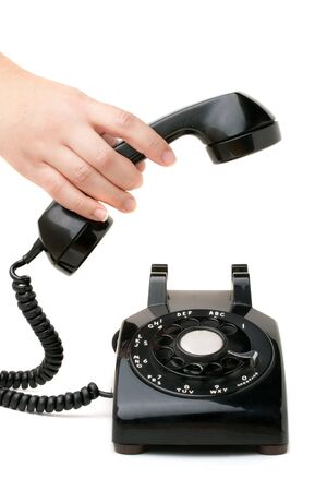 A hand  holding the handset of an old black vintage rotary style telephone isolated over white. photo