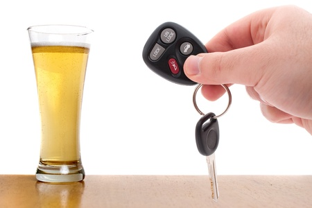 Drunk driving concept image with a hand holding some car keys and a glass of beer isolated over a white background.  Archivio Fotografico