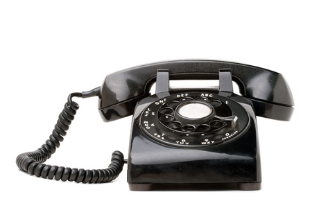 black appliances: An old black vintage rotary style telephone isolated over a white background.