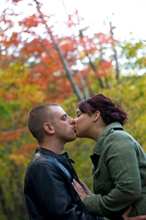 passionately: A young happy couple passionately kissing each other outdoors during fall or autumn. Stock Photo