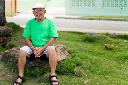 A older Hispanic senior citizen man sits outdoors in a tropical setting.  photo