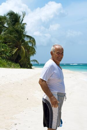 elder tree: A older Hispanic senior citizen man standing on a tropical beach in the Caribbean.