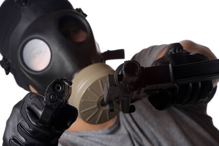 A man wearing a gas mask pointing two guns at the viewer. Shallow depth of field.  Works great for crime or warfare concepts. photo