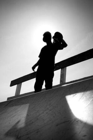 skateboarding: Silhouette of a young teenage skateboarder at the top of the half pipe ramp at the skate park.