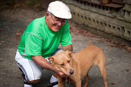 An elderly Hispanic senior citizen man petting his dog with a large smile on his face. photo