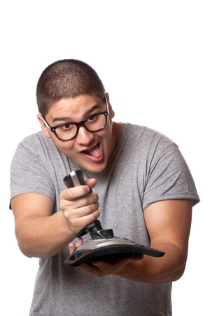 dork: A fun loving video gamer playing with a wireless joystick over a white background. Stock Photo