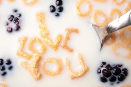 De woorden I LOVE YOU uiteengezet van de brief vormige granen stukken drijvend in een met melk gevulde granen kom. Stockfoto