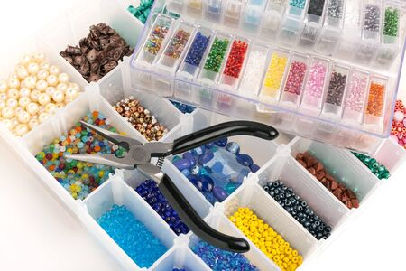 An organizer full of multi colored beads and tools for making jewelry and crafts. photo