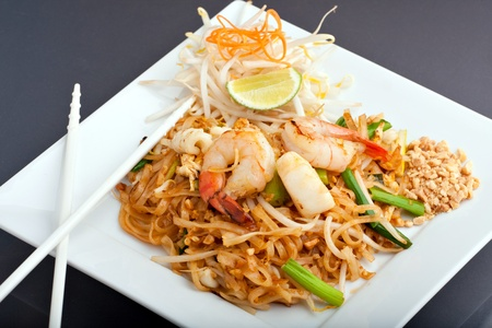 Seafood pad Thai dish of Thai fried rice noodles on a square white plate with chopsticks and grated carrot garnish.