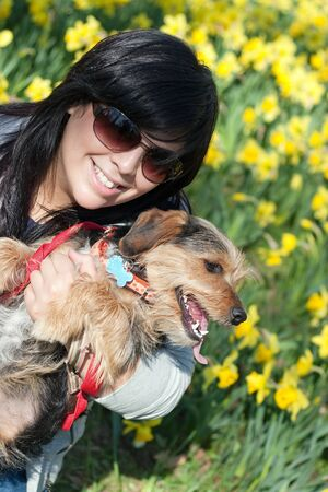 beagle mix: A cute terrier mix breed pup in the arms of a beautiful Spanish woman posing in front of the yellow daffodil flowers in the Spring time. Stock Photo