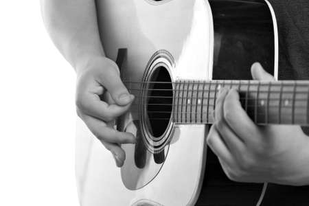 solo: Closeup of a mans hands strumming and electric acoustic guitar isolated over a white background.
