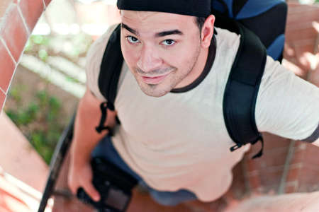 late twenties: A young photographer in his late twenties with his camera backpack and dslr in hand walking down a spiral staircase. Shallow depth of field.