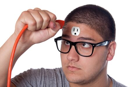 Conceptual image of a young man holding an electrical chord unplugged from the outlet on his forehead.