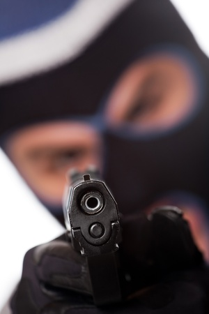 ski mask: An angry looking man wearing a ski mask pointing a black handgun at the viewer. Shallow depth of field.
